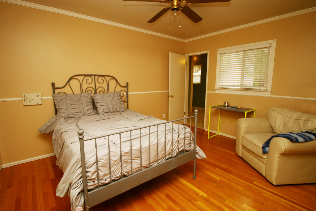 Master bedroom with extra closet space, hardwood floors, and doorway to private bathroom.