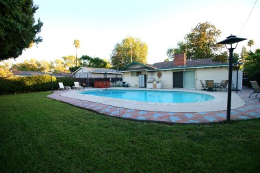 Gorgeous backyard with inground pool, and lots of grassy area for kids and pets to play