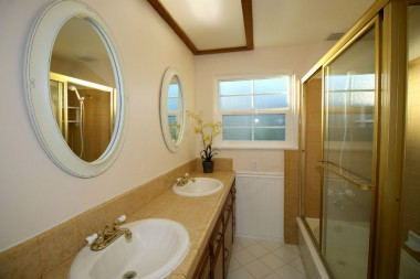 Double sinks, tiled counter top, tile flooring, charming beadboard, and shower in tub.