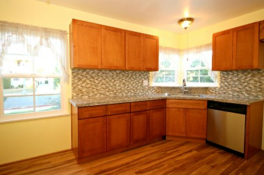 Remodeled kitchen with granite counter top, glass tile back splash, dishwasher, vinyl plank flooring, and corner sink. Cute and functional as can be!