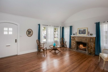 Spacious living room with barrel ceiling, refinished original hardwood floors, and lots of natural light!