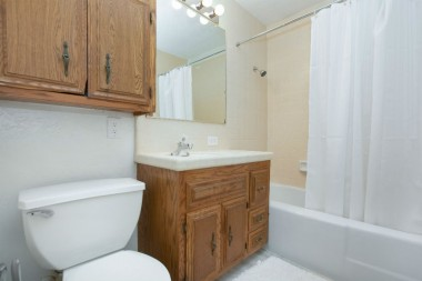 Guest house full bathroom with shower in tub.