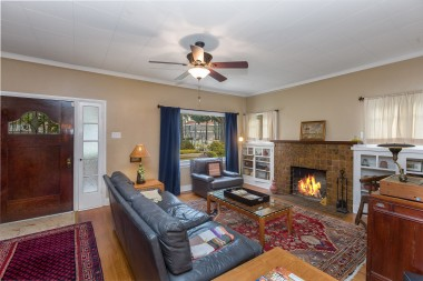 Gorgeous original hardwood floors, gas and wood-burning fireplace, ceiling fan, and original front door.