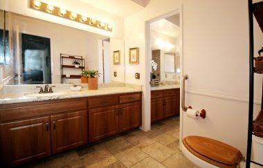 Second main floor half bathroom with tile floor and granite counter. Inside doorway leads to master bathroom.