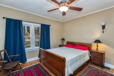 Front bedroom with original hardwood floors and ceiling fan.