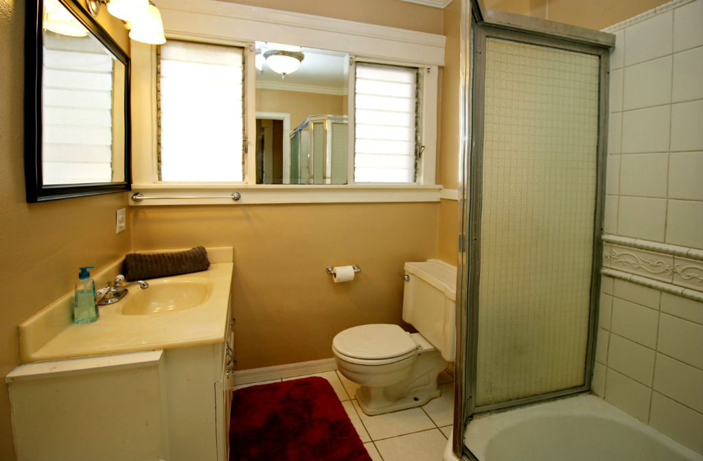 Hall bathroom with tiled shower in tub.