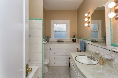 Full hallway bathroom with built-in cabinetry.