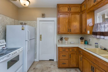 Kitchen with lots of cabinetry, dishwasher, and swinging door to formal dining room.