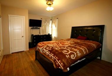Master bedroom with original hardwood floors and private half bathroom.