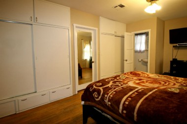 Alternate view of master bedroom, with two sets of closets, and view into the half bath.