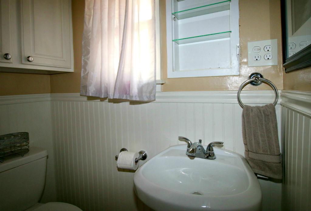 Master half bath with bead board and pedestal sink.