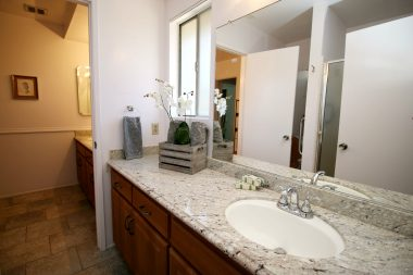 Master bathroom with shower, tile floor, and granite counter top.