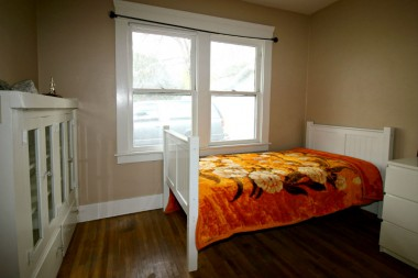 Middle bedroom with original hardwood floors and original built-in shelving unit.