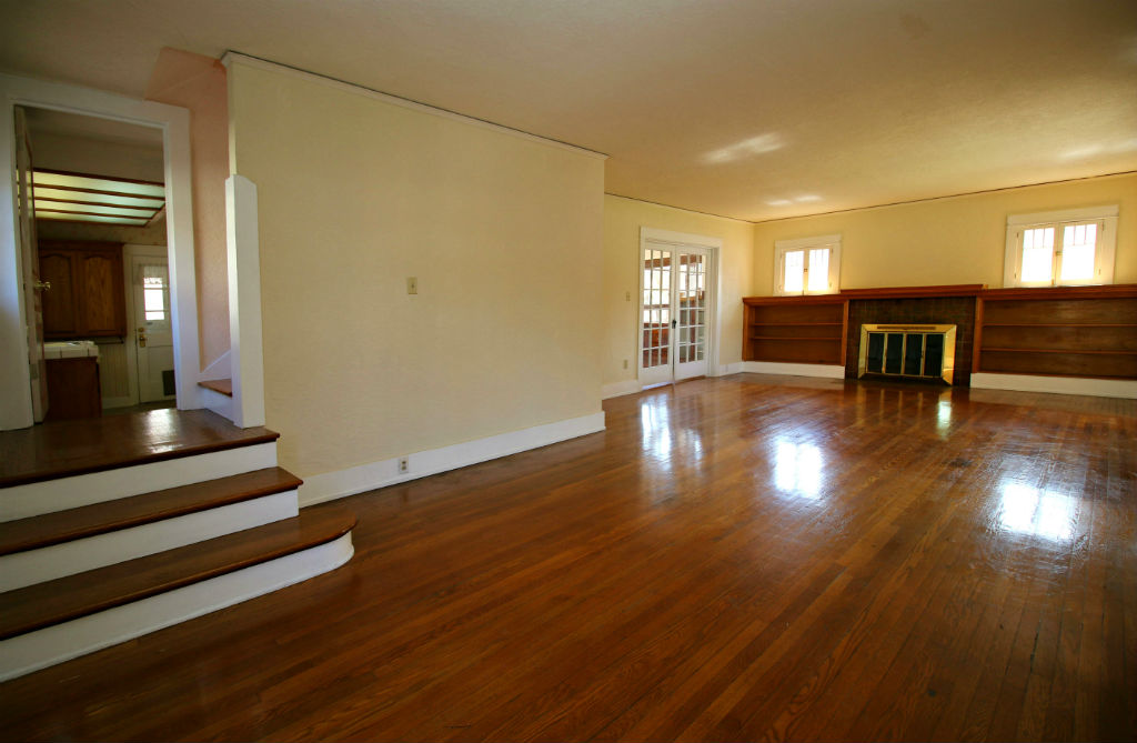 Spacious living room with original hardwood floors and fireplace.