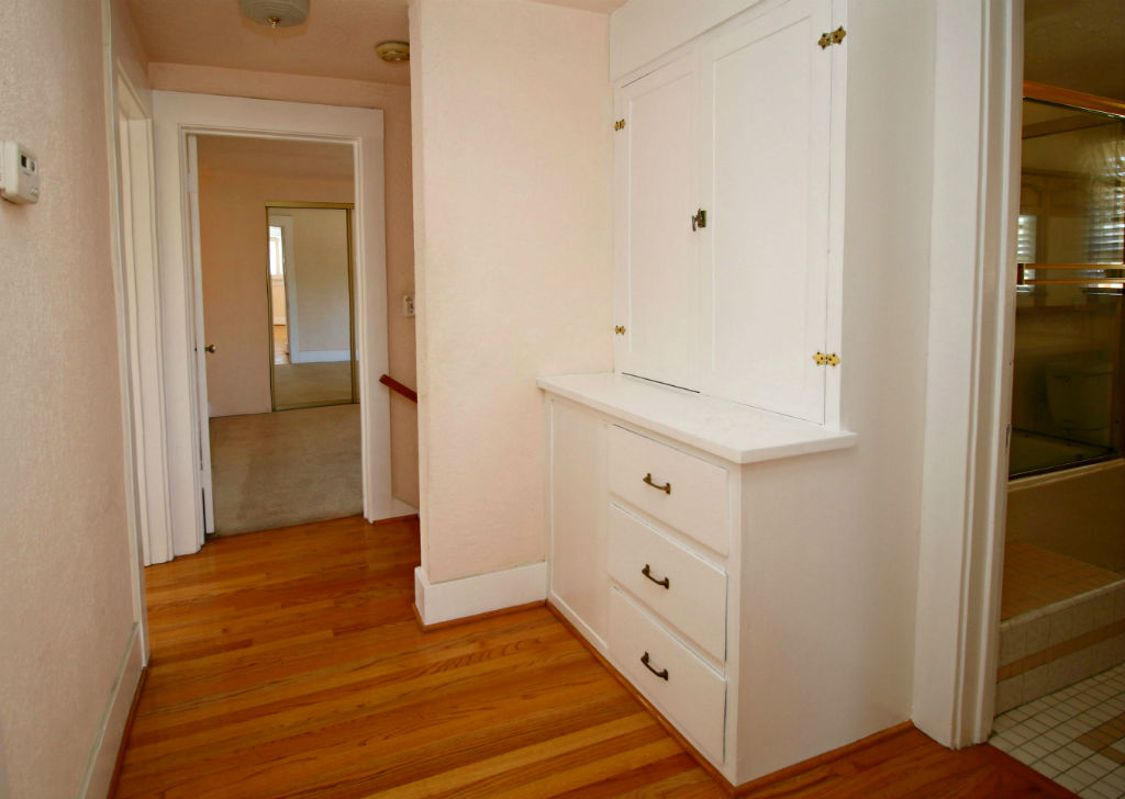 Upstairs hallway with linen closet and newer oak floors.