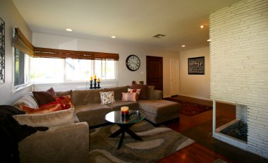 Spacious mid-century open-concept living room with corner fireplace and refinished hardwood floors.