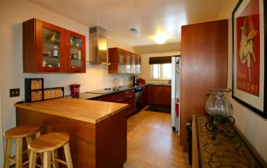 Remodeled kitchen with newer cabinets, double oven, dishwasher, and breakfast bar.