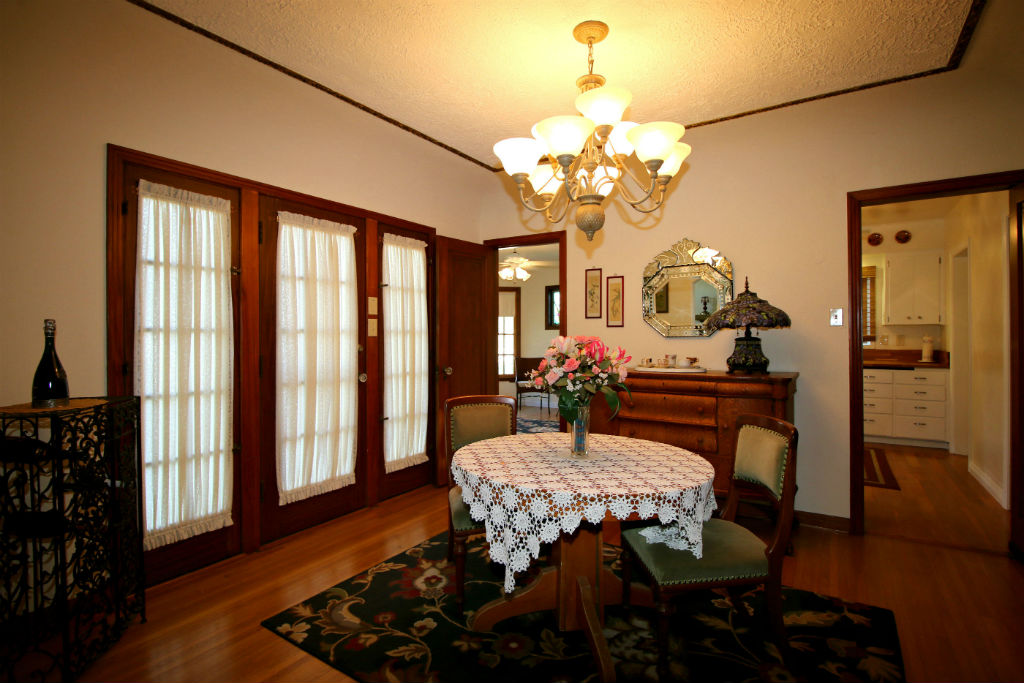 Formal Dining Room With Coved Ceiling And French Door Leading To Side Courtyard Refinished Original Hardwood Floors