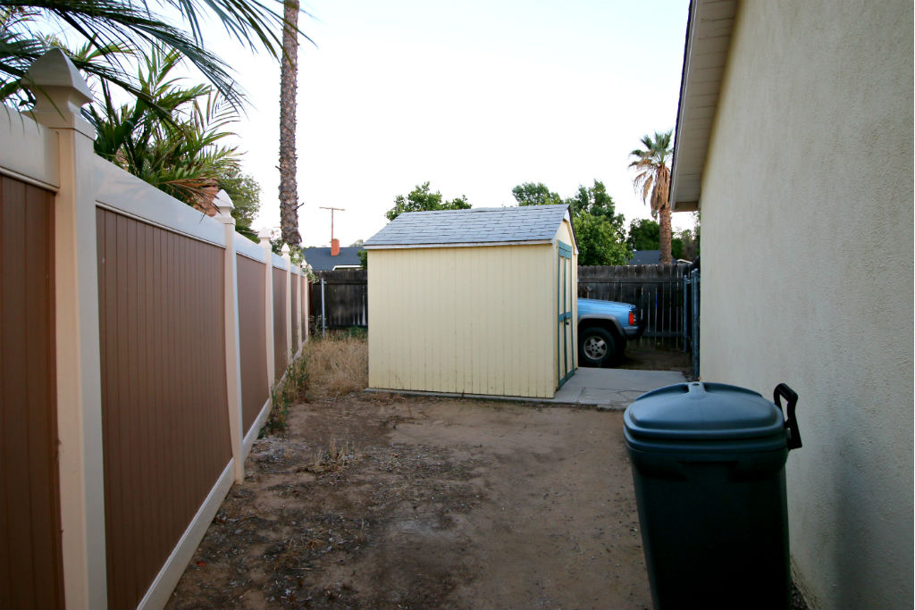 Gated RV/boat parking area on side of house with shed.