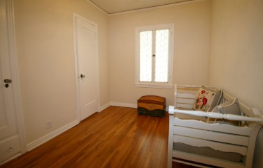 Third bedroom with original hardwood floors and doorway leading to second bathroom.