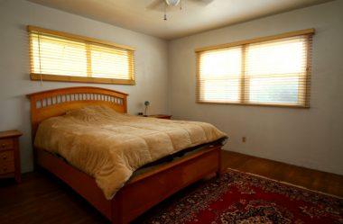 Back bedroom with ceiling fan and original hardwood floors.