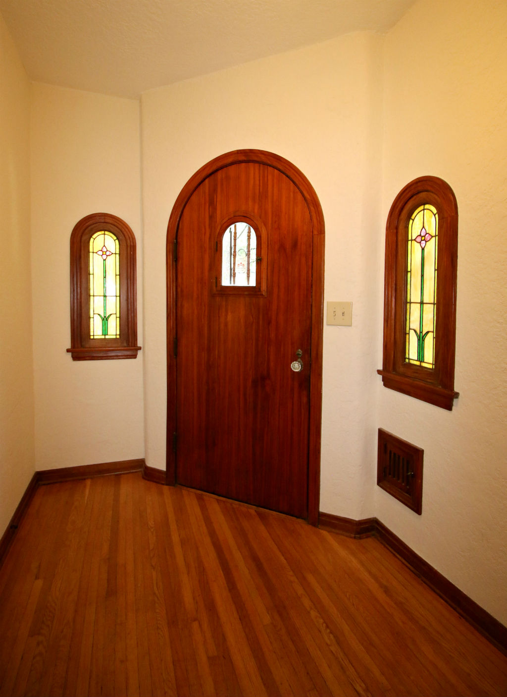 Entry door flanked by stained glass windows and mail slot.