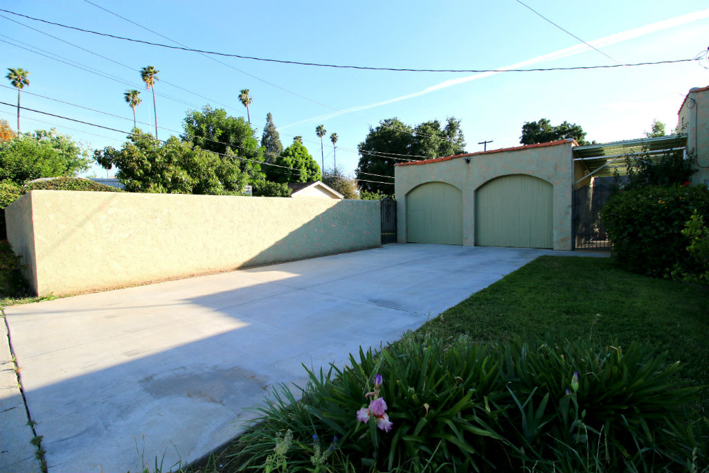 2-car detached garage with lots of driveway space for RV parking. On the other side of the stucco wall is the huge pool-sized yard.