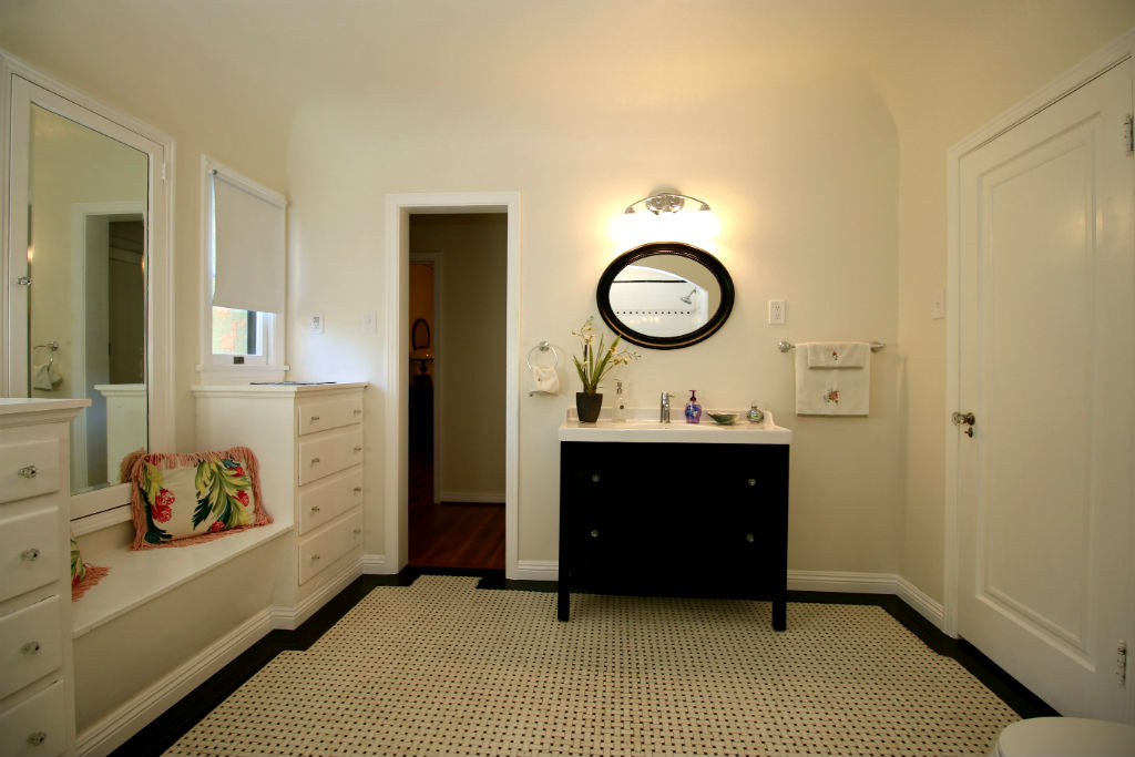 Alternate view of bathroom with original basket weave tile floor and original cabinetry. Newer vanity and light fixture.