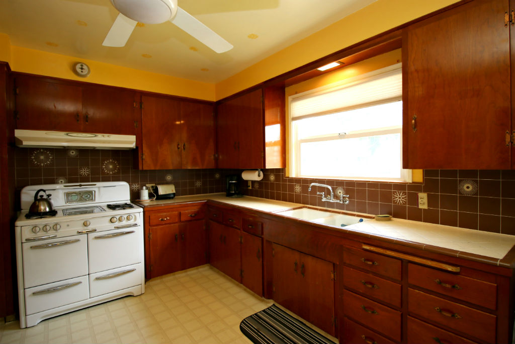 Retro kitchen with original 1950s back splash tile that is back in style. Antique Wedgewood stove is included.
