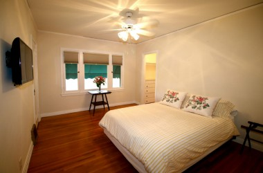 Middle bedroom with refinished original hardwood floors and a walk-in closet with built-in chest of drawers. TV stays.