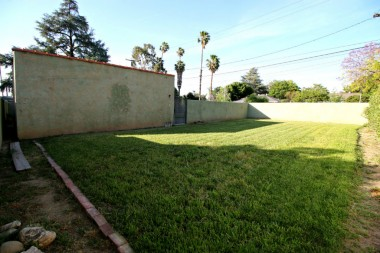 Huge private and pool-sized yard completely enclosed with stucco wall.
