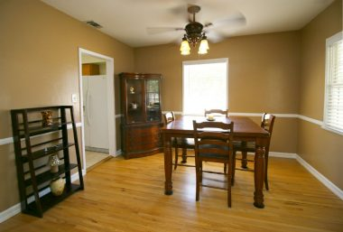 Formal dining room with ceiling fan and recently refinished hardwood floors.