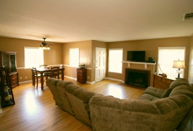 Large living room with recently refinished hardwood floors, fireplace, and dining room.