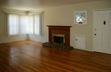 Light and bright living room with lovely original hardwood floors, fireplace, and convenient wood storage for winter evenings in front of the fireplace.