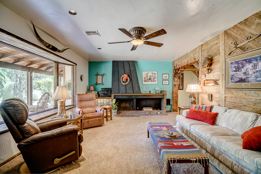 Alternate view of Living Room with gas and wood-burning fireplace and recessed lighting.