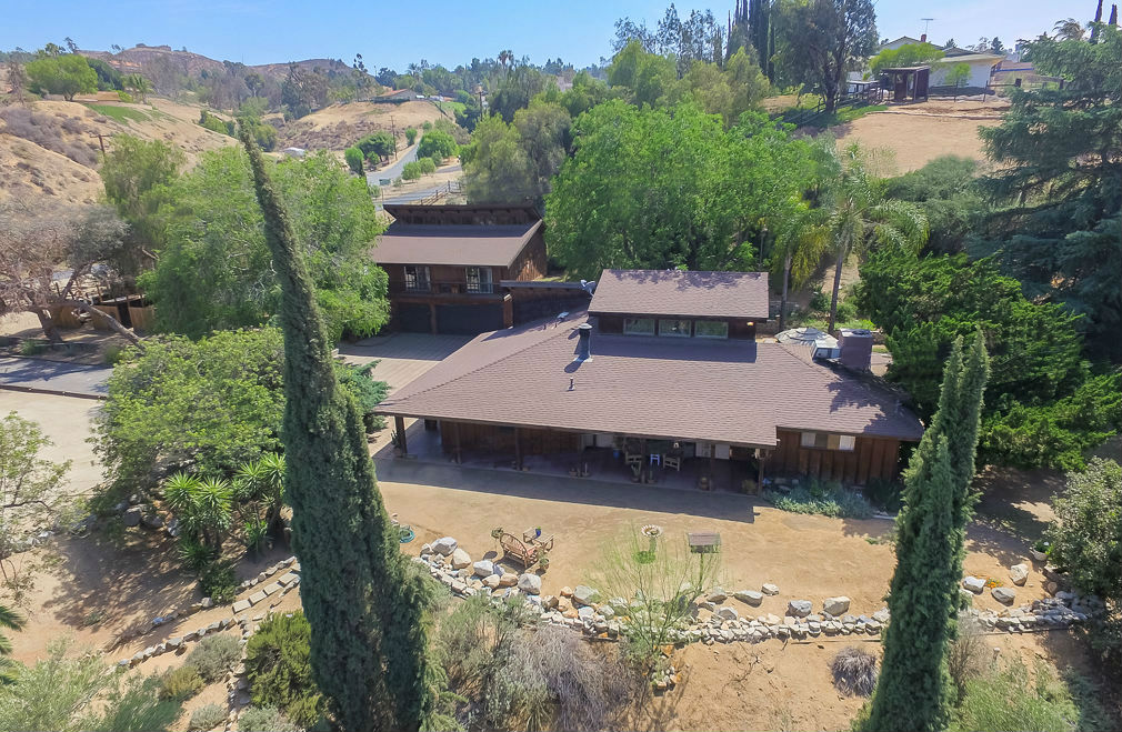 Aerial photo of main house and guest quarters over the 3-car garage. Almost every rock on this property has its place among the walking paths and orchard. This estate is a true gem!