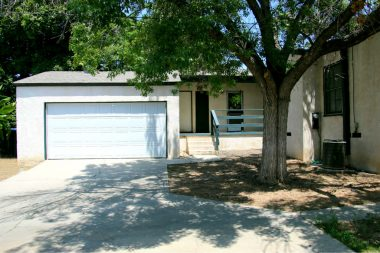 Drive through the gate into the backyard for access to the attached 2-car garage with auto roll-up door, laundry, and back porch. Mature shade trees, gated RV parking, and large pool-size yard.