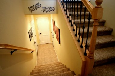 Another view of the stairway with 3 doors at the bottom: front entry door to the left, a coat closet straight ahead, and access to the garage on the right.