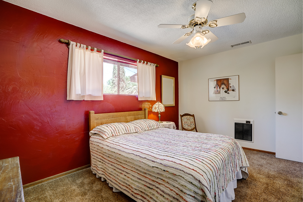 Front bedroom on other side of the house, with carpeting and ceiling fan.