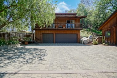 3-car garage with permitted and lovely guest quarters above with balcony. Note the lovely driveway pavers too.