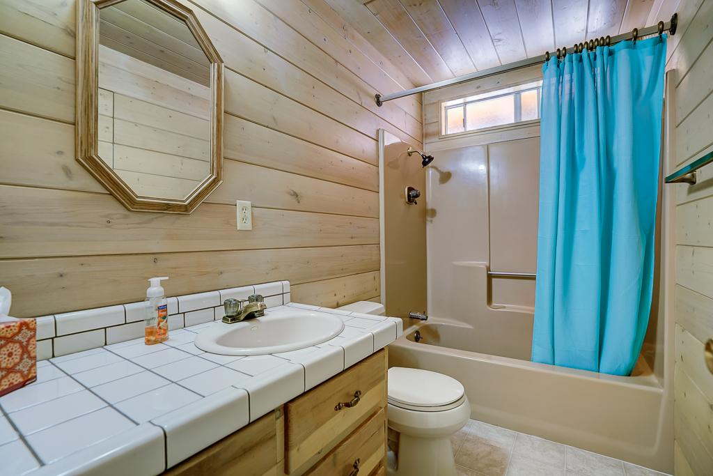 Guest quarters full bathroom with new linoleum flooring.