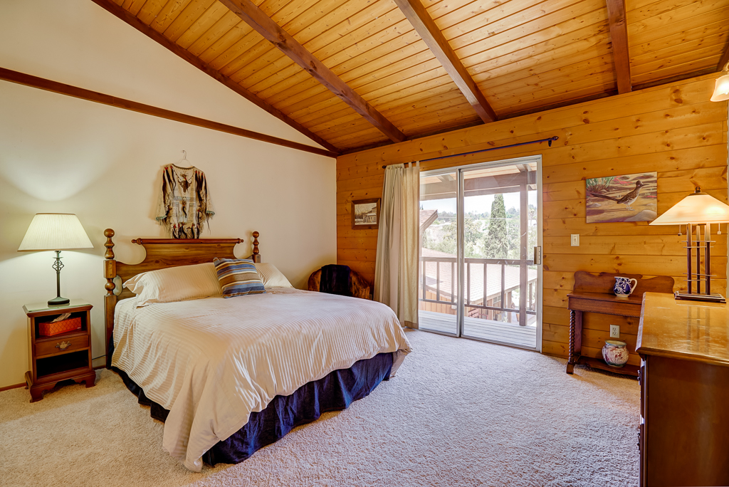 Huge guest quarters bedroom with wood beam cathedral ceiling and slider to balcony. This room also has a gigantic walk-in closet.