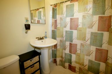 Updated hallway bathroom with pedestal sink, tiled tub/shower, and tile flooring.