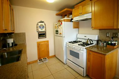 Remodeled kitchen with granite counters, tile floor, dishwasher and gas stove.