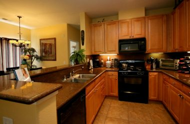Lovely remodeled kitchen with tile flooring, granite counter tops, dishwasher, gas stove, built-in microwave, and breakfast bar.