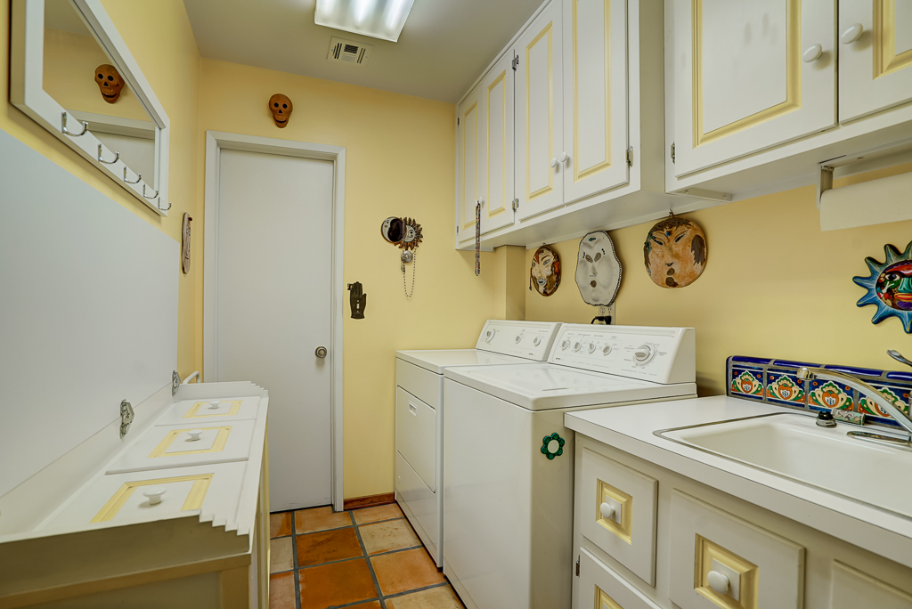 Bright laundry room with lots of cabinetry, utility sink, and folding table that lifts up to expose 3 separate laundry bins.