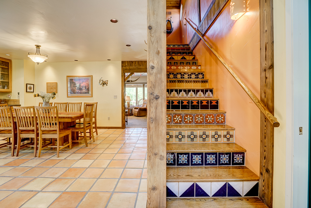 Stairs to loft over kitchen, with custom tiles that current homeowner made herself!