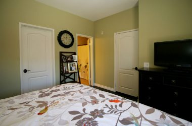 Alternate view of master bedroom with walk-in closet to left, full private bathroom, and door to hallway.