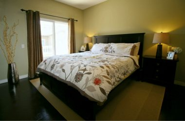 Master bedroom suite with walk-in closet, engineered hardwood floors, private balcony, and private full bath. King-size bed pictured.