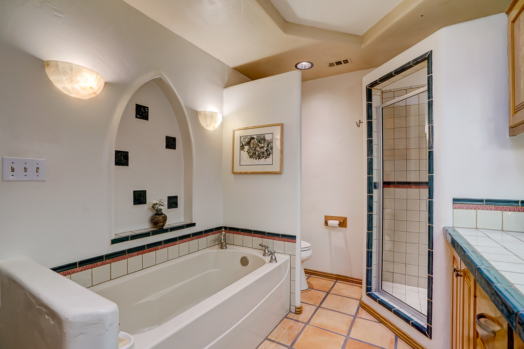 Alternate view of master bathroom with soaking tub and Saltillo tile flooring.